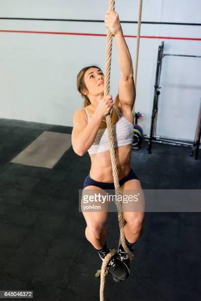 Sportswoman climbing a rope