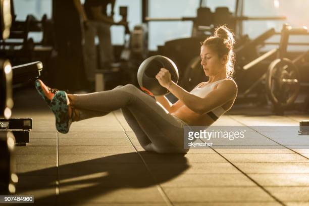 sportswoman doing sit-ups with medicine ball on sports training in a gym. - one young woman only stock pictures, royalty-free photos & images