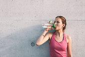 sportswoman drinking water in front of concrete wall