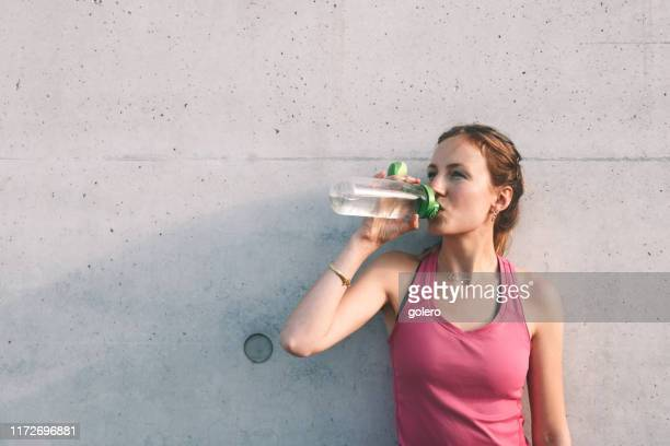 sportswoman drinking water in front of concrete wall - desporto imagens e fotografias de stock
