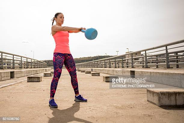 sportswoman exercising with kettlebell on the bridge - swinging stock pictures, royalty-free photos & images