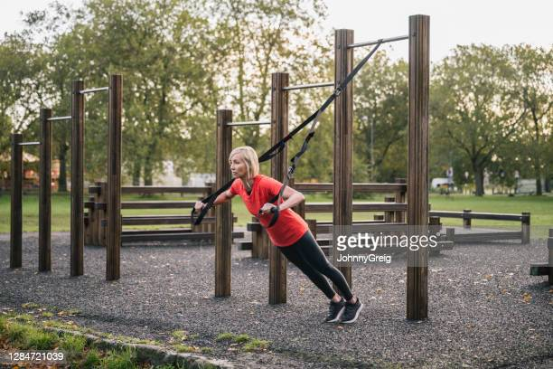 sportswoman in early 50s doing outdoor suspension training - clapham common stock pictures, royalty-free photos & images