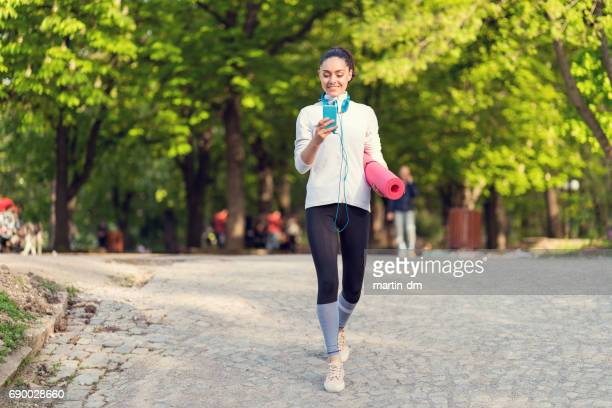 Sportswoman in the park texting on smartphone
