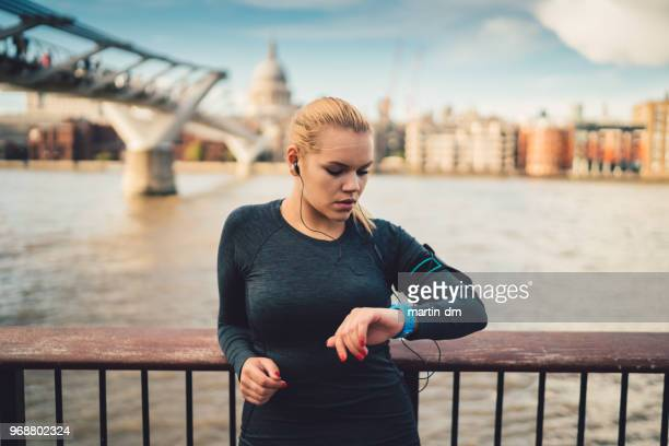 sportswoman in uk checking pulse on smart watch during workout - fitness tracker stock pictures, royalty-free photos & images