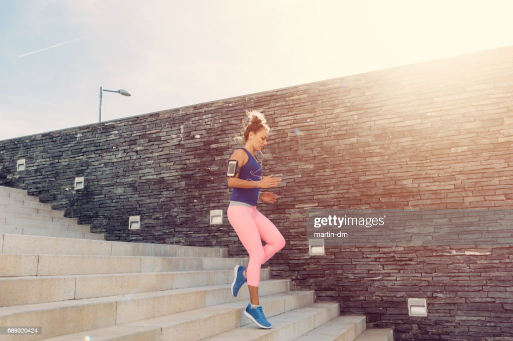 Sportswoman jogging downstairs : Stock Photo