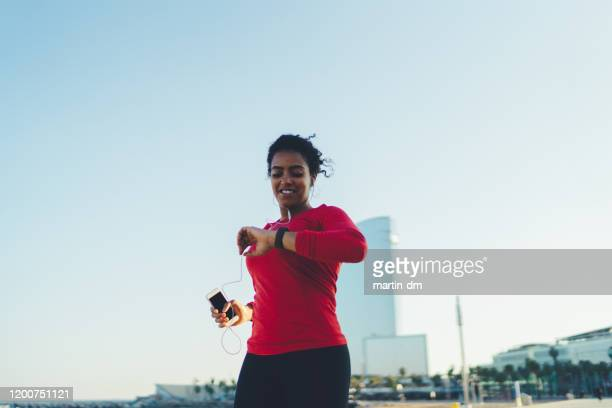 sportswoman jogging in barcelona - fitness tracker stock pictures, royalty-free photos & images