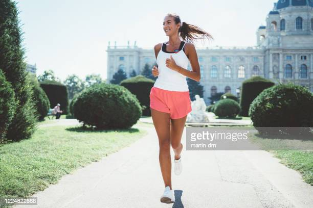 sportswoman jogging in the city park - running shorts stock pictures, royalty-free photos & images