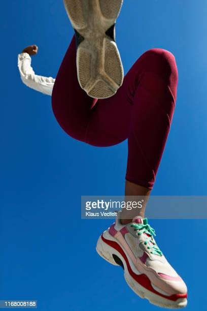 sportswoman jumping against clear blue sky - blue shoe stock pictures, royalty-free photos & images
