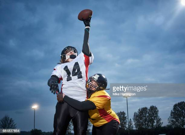 sportswoman jumping to reach for ball - safety american football player stock pictures, royalty-free photos & images