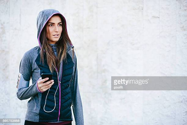 Sportswoman listening music from her phone
