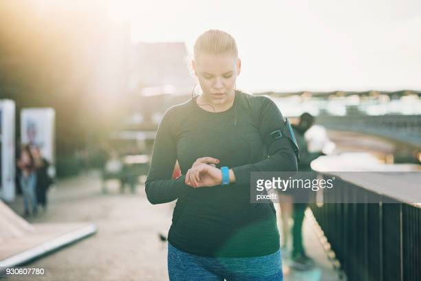 sportswoman looking at her smart watch - checking sports stock pictures, royalty-free photos & images