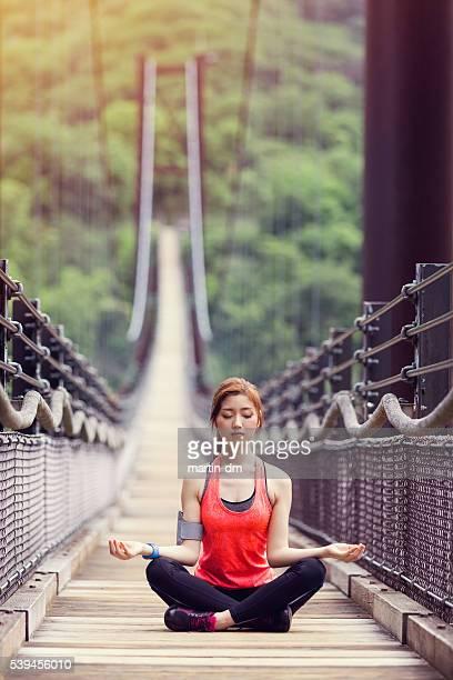 Sportswoman practicing yoga at the rope bridge