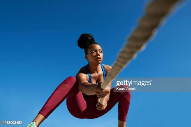 sportswoman pulling rope against clear blue sky on sunny day - schwarze hosen stock-fotos und bilder