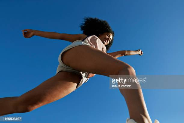 sportswoman running against clear blue sky during sunny day - blue shorts stock pictures, royalty-free photos & images