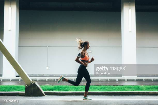 sportswoman running in the city - center athlete stock pictures, royalty-free photos & images
