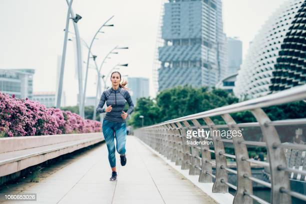 sportswoman running on bridge - center athlete stock pictures, royalty-free photos & images