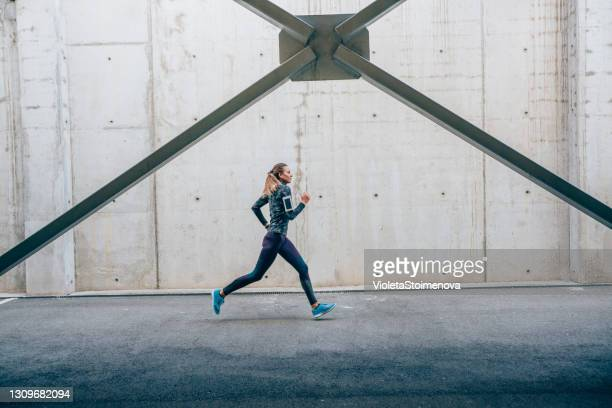 sportswoman running outdoors - trousers stock pictures, royalty-free photos & images