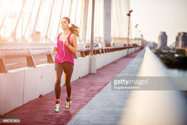 Sportswoman running over the bridge in the morning