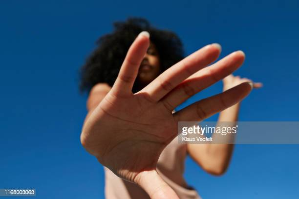 sportswoman showing stop gesture against clear blue sky - ストップ ストックフォトと画像