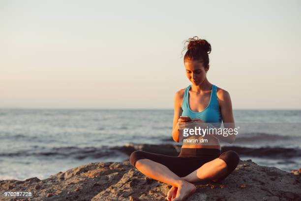 Sportswoman sitting at the sea rocks and texting