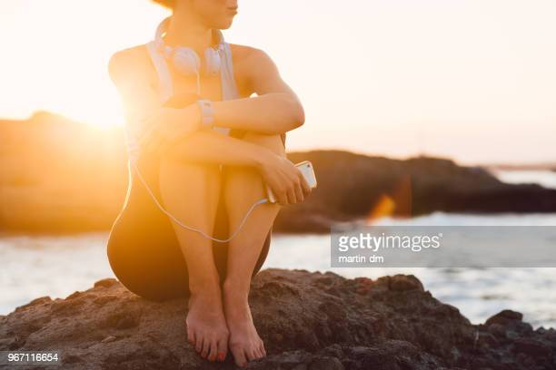 sportswoman sitting at the sea rocks on sunset - solar flare stock pictures, royalty-free photos & images