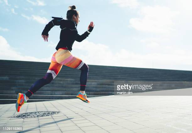 sportswoman sprinting in the city - sportswear stock pictures, royalty-free photos & images
