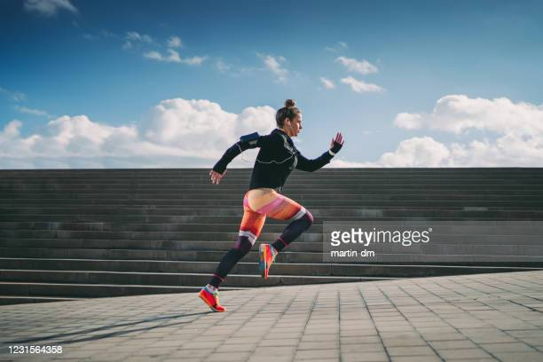sportswoman sprinting in the city - jogging stock pictures, royalty-free photos & images