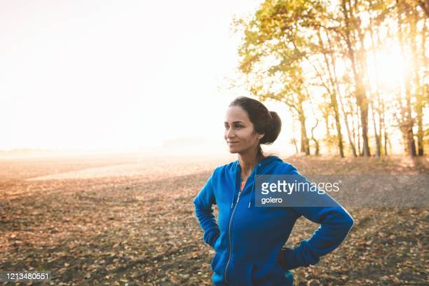 sportvrouw die zich op gebied bij zonsopgang bevindt - mid volwassen stockfoto's en -beelden