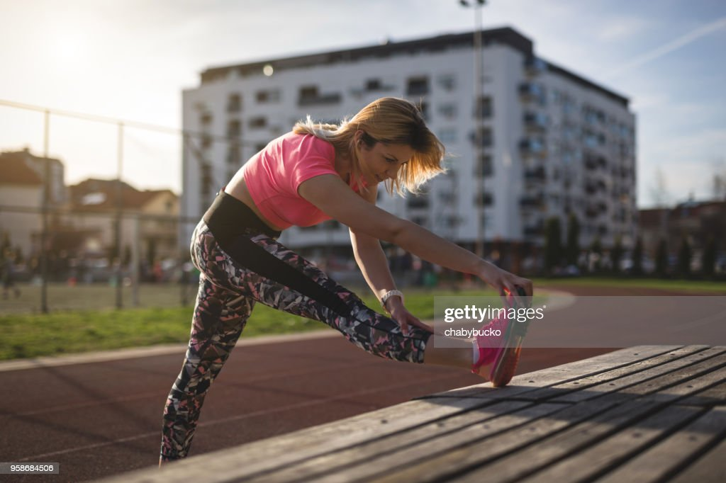 Sportswoman stretching legs : Stock Photo