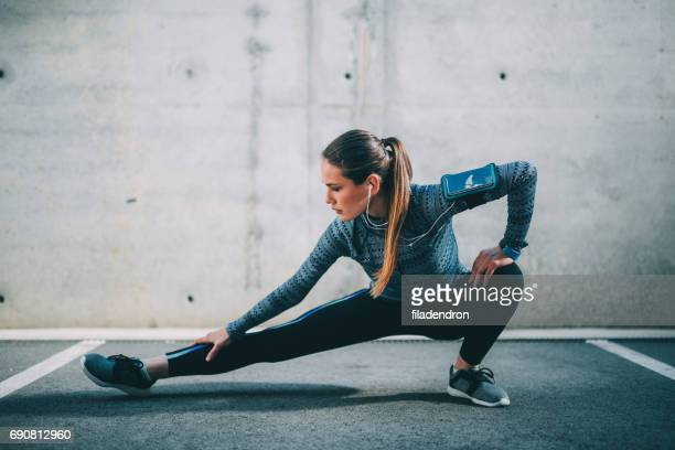 sportswoman stretching outdoors - stretching stock photos and pictures