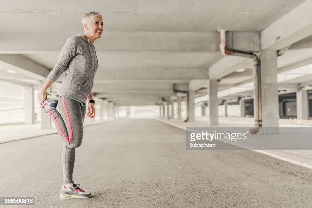 sportswoman stretching - older woman legs stock photos and pictures