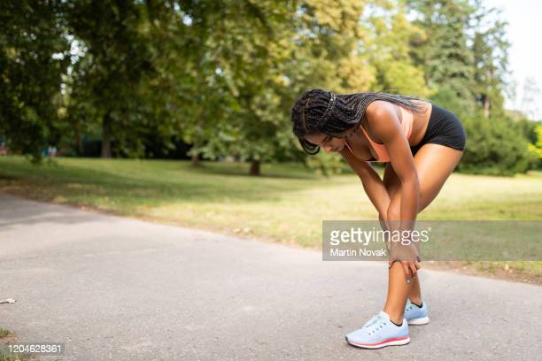 sportswoman suffering from leg cramp due to overtraining - injured stock pictures, royalty-free photos & images