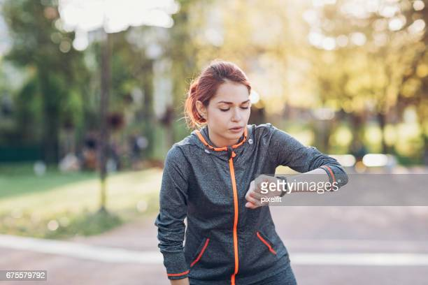 Sportswoman taking break and checking her smart watch