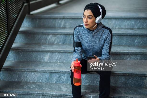 sportswoman taking break on a staircase. - modest clothing stock pictures, royalty-free photos & images
