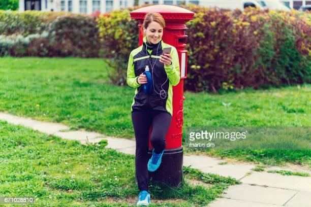 Sportswoman texting on smartphone