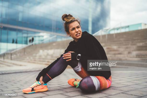 sportswoman with broken leg sitting on ground,barcelona - injured stock pictures, royalty-free photos & images