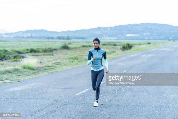 Sportswoman with hijab jogging on road near the sea