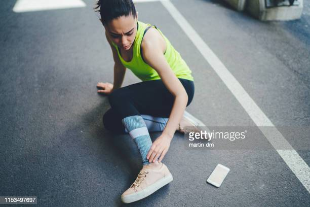 sportswoman with injured ankle - twisted stock pictures, royalty-free photos & images