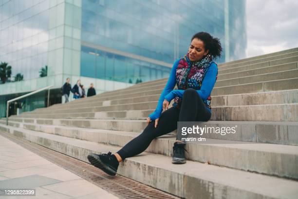 sportswoman with knee fracture - black trousers stock pictures, royalty-free photos & images