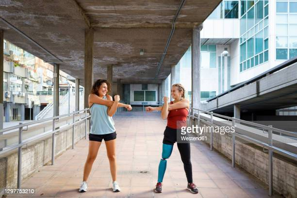 sportswoman with prosthetic leg exercising with friend while standing on bridge - persons with disabilities stock pictures, royalty-free photos & images