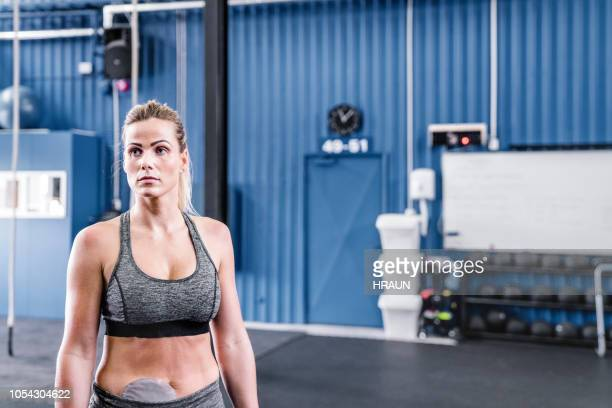 sportswoman with stoma bag in gym - colorectal cancer stock photos and pictures