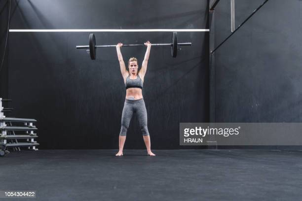 sportswoman with stoma bag picking up heavy barbell at gym - snatch weightlifting stock photos and pictures