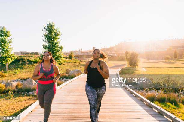 sportswomen jogging on boardwalk against clear sky at park - voluptuous stock pictures, royalty-free photos & images