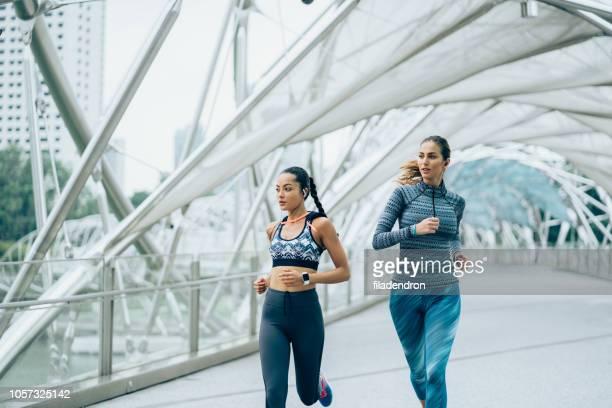 sportswomen jogging on bridge - center athlete stock pictures, royalty-free photos & images