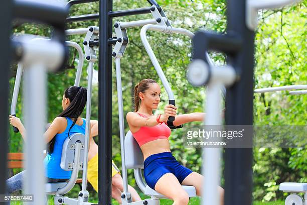 Sportswomen practicing on chest press in the park
