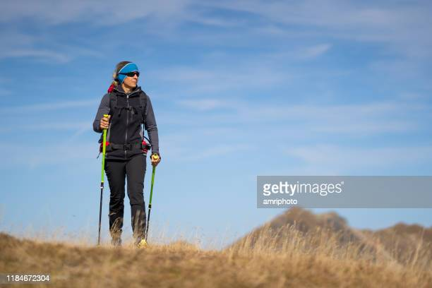 sporty 45 years woman hiking alone over dry grass on windy autumn day high up in the mountains - 45 49 anni foto e immagini stock