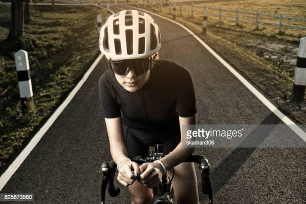 Sporty Asian Cyclist take a rest after cycling on track with mountain and beautiful sky background