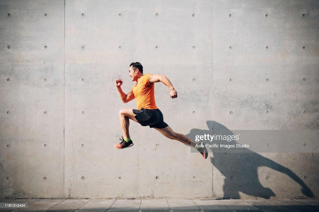 スポーティなアジアンミッドマンが走り、シャッターに跳ね上がった。健康とフィットネスの概念。 : ストックフォト