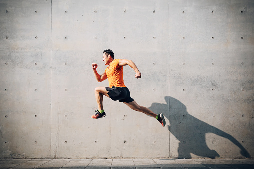 Sporty Asian Mid man running and jumping against shutter. Health and fitness concept. 1161313454