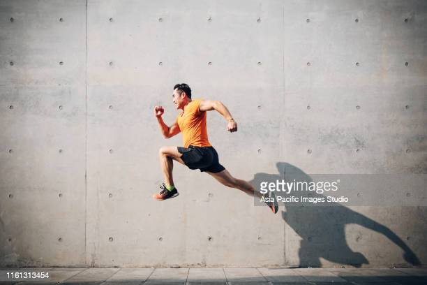 sporty asian mid man running and jumping against shutter. health and fitness concept. - competition stock pictures, royalty-free photos & images